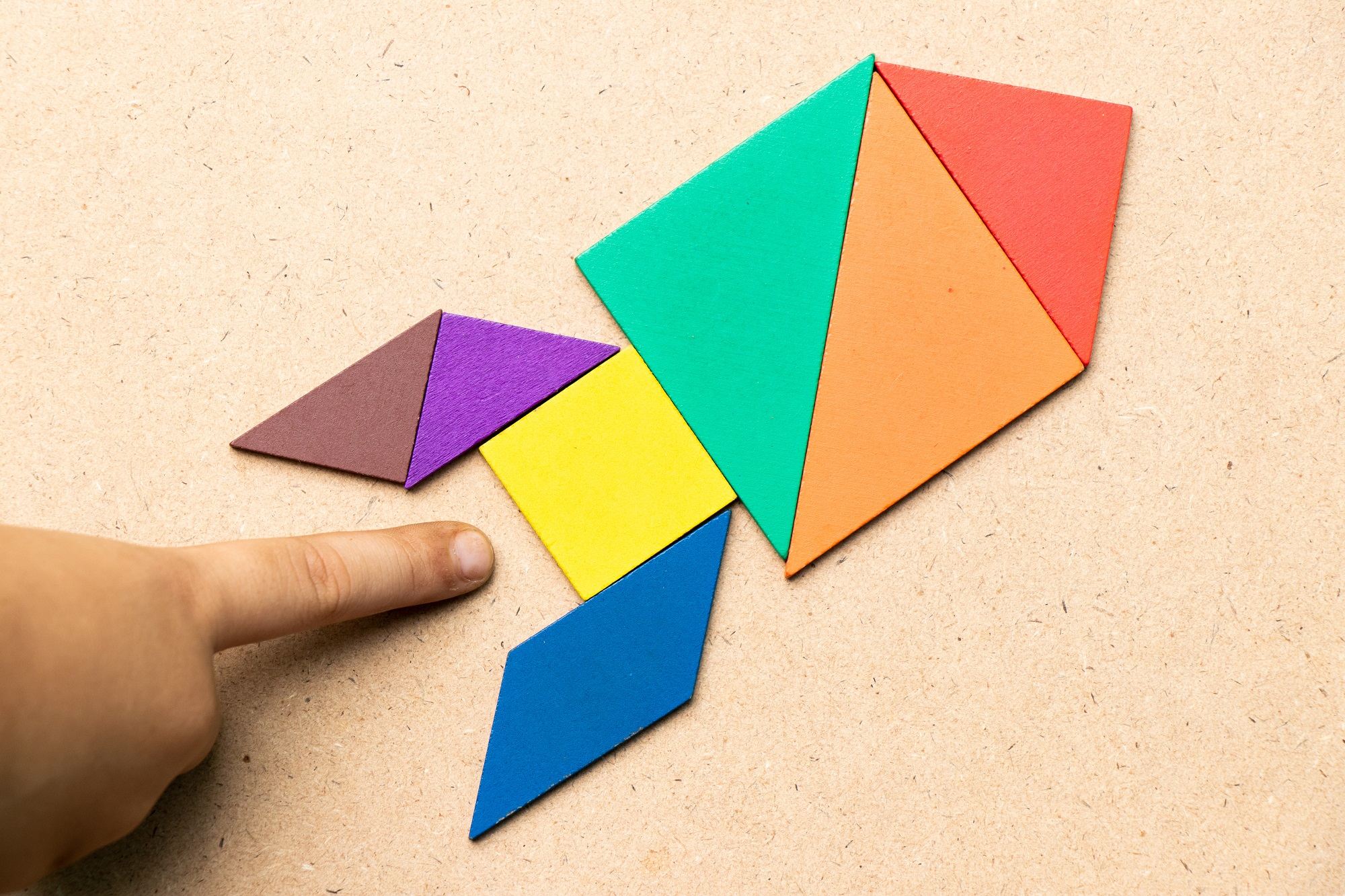 A child's hand near a colourful paper puzzle in the shape of a rocket